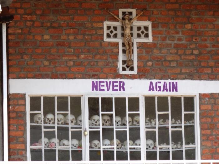 Never_Again_-_With_Display_of_Skulls_of_Victims_-_Courtyard_of_Genocide_Memorial_Church_-_Karongi-Kibuye_-_Western_Rwanda_-_01